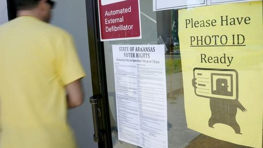 "In this May 5, 2014, file photo, a voter walks past a ""Please Have Photo ID Ready"" sign as he enters an early-voting polling place in downtown Little Rock, Ark. In a unanimous ruling, the Arkansas Supreme Court Wednesday, Oct. 15, 2014, found that the state's voter identification law is unconstitutional."