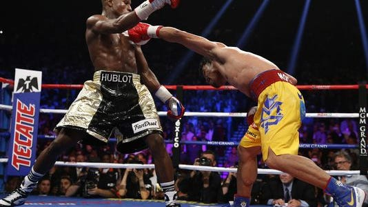 Manny Pacquiao, from the Philippines, right, hits Floyd Mayweather Jr., during their welterweight title fight on Saturday, May 2, 2015 in Las Vegas.