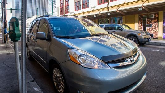 An minivan used by an Uber X driver is parked in downtown Lafayette, Louisiana. D.C. police are asking for help finding a man they say assaulted and kidnapped a woman while driving a car with an Uber decal.