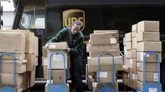 In this March 10, 2011, file photo, a United Parcel Service driver unloads packages from a truck and arranges them for delivery in New York. UPS will pay nearly $26 million to New Jersey and the United States to resolve allegations it concealed late deliveries on overnight packages to federal and state government agencies.