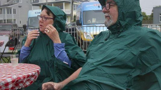 With the proper rain gear, Patty and Gary Ketchersid of Montville, NJ enjoy a rest between walking the boardwalk length during Lobsterfest in Bradley Beach NJ on June 27, 2015.
