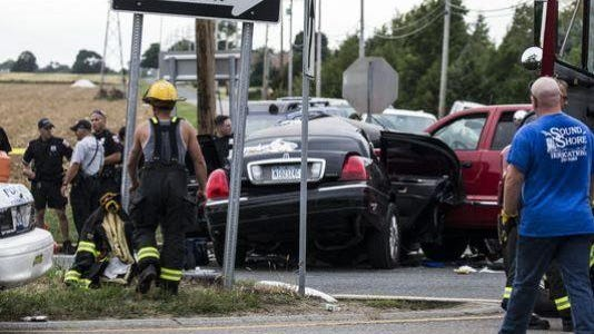 Authorities investigate the scene after a fatal crash between a limousine and a pickup truck Saturday, July 18, 2015, in Cutchogue, New York.