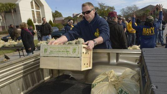 Volunteers help distribute free food at a previous Farm Share event.