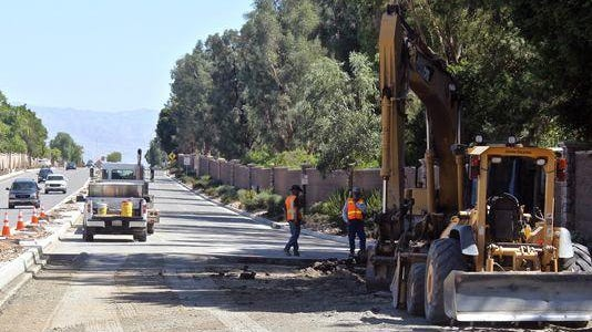 Workers make repairs on Fred Waring Drive in Indian Wells. The road may reopen Tuesday evening after it shut down because of a leaky water line.