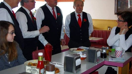 Members of Ra-Cha-Cha, from left, Ed Rummler, Dave Bay, Lee Shepter and Mike McKain deliver a Singing Valentine at a restaurant in Irondequoit last year.