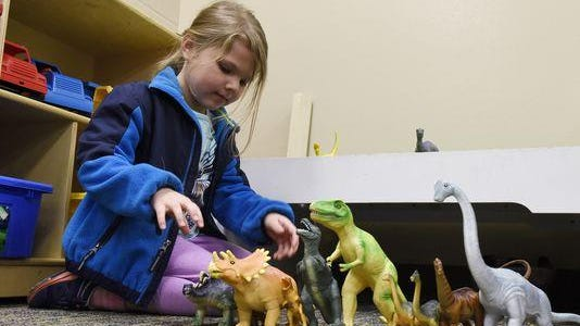 Marley Nelson plays with dinosaurs during an open house for Learning Adventures preschool at Harvey Dunn Elementary School, April 7, 2016.