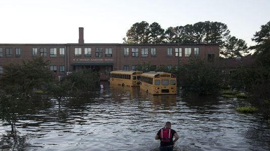 A volunteer firefighter makes his way through floodwaters left by rains from Hurricane Matthew to turn off the lights of a school bus in front of W.H. Knuckles Elementary School in Lumberton.
