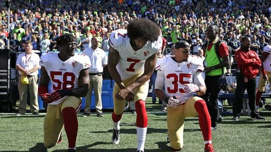 San Francisco 49ers Eli Harold (58), Colin Kaepernick (7) and Eric Reid (35) drop to a kneeling position at the beginning of the national anthem before an NFL football game against the Seattle Seahawks, Sunday, Sept. 25, 2016, in Seattle.