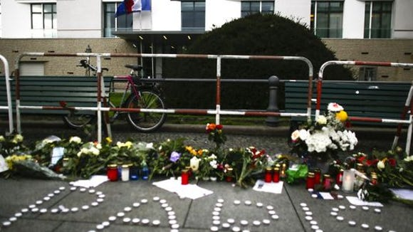 lowers and candles are placed in front of the French Embassy in Berlin, on Nov. 14, 2015. (Photo: Markus Schreiber, AP)