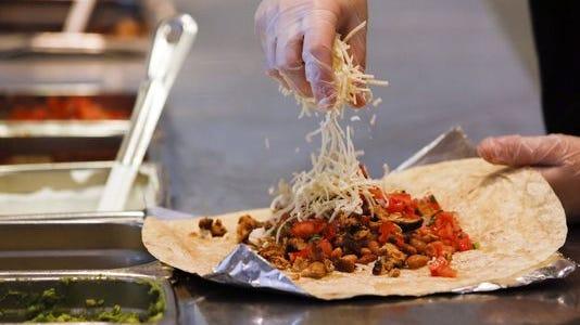 A worker prepares a burrito at Chipotle Mexican Grill.