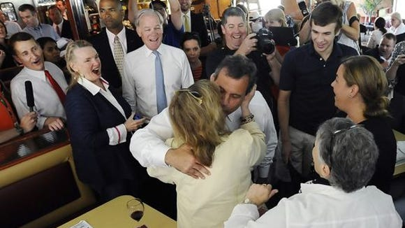 Gov. Chris Christie (center), in Connecticut to campaign for GOP gubernatorial candidate Tom Foley (back center), kisses Paula Murray as Murray's friend Mary Ann Springall looks on Monday at a Greenwich diner in July. (AP photo)