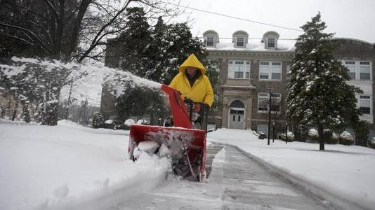 Anton Goral, the custodian at Woodbury Junior/Senior High School, clears the walkways around the school during a storm on February 13, 2014.