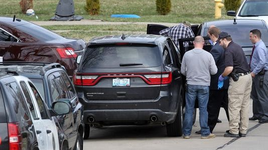 Investigators interview an unidentified person outside 19 Bon Jan Lane Monday afternoon.