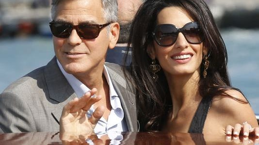 George Clooney, left, and Amal Alamuddin arrive in Venice ahead of their weekend wedding.