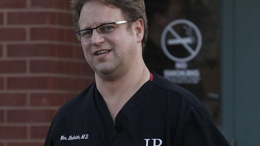 Dr. William Hedrick walks out of his pain clinic at 3301 Fox Ridge Lane after members of the DEA, Attorney General's office and local agencies raided it Monday evening.