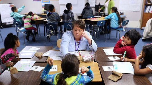 Becky Ketner, an English as a second language teacher, instructs a class as Carola Krebs, in background, teaches another ESL class in the same classroom at John Colemon Elementary in Smyrna. Educational Assistant Marina Lowe also uses the same classroom to teach English to students one on one.