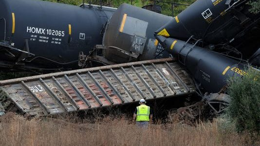 A CSX employee examines the wreckage of train cars that derailed on Hwy 90 east of Paddle Wheel Dr. in Milton Sunday morning.