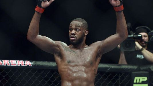 Jon Jones begins to celebrate after retaining the UFC light heavy weight championship against Glover Texeira at Baltimore Arena.