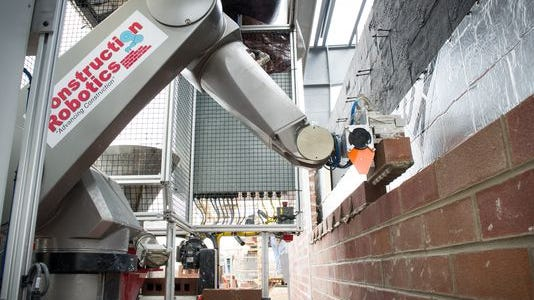 A Construction Robitics' robot lays bricks for a wall at a site in Victor. The company is a small start-up business that has won major industry awards.