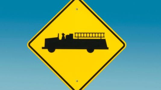 Yellow road sign depicting fire truck.