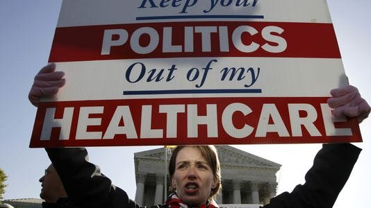 An opponent of health care reform demonstrates in front of the Supreme Court.