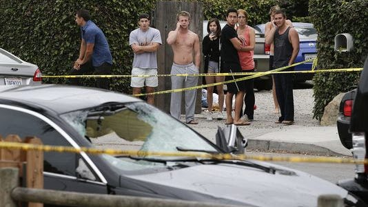 People look at a black BMW sedan driven by a drive-by shooter on May 24, 2012 in Isla Vista, Calif.