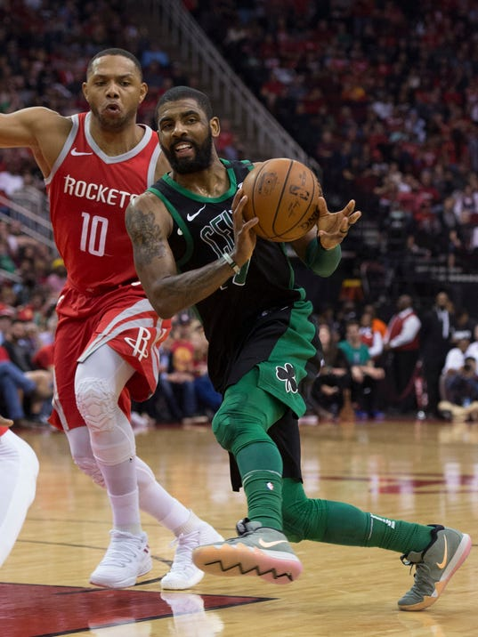 Boston Celtics guard Kyrie Irving (11) passes the ball as he drives against Houston Rockets guard Eric Gordon (10) during the second half of an NBA basketball game Saturday, March 3, 2018, in Houston. (AP Photo/George Bridges)