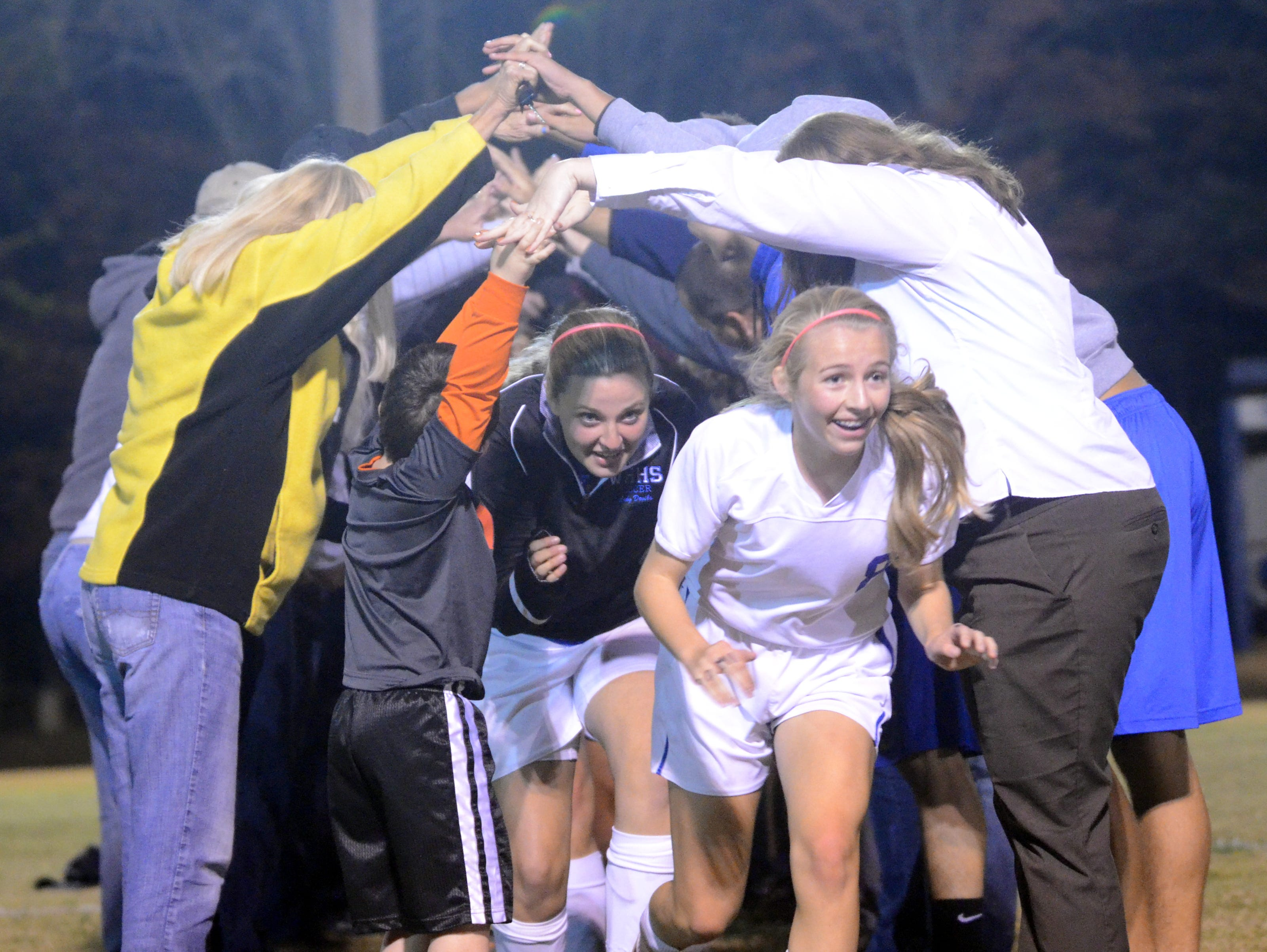 The White House High girls soccer players run through a tunnel made by their parents and fans following Tuesday evening's 4-1 victory over visiting Hume-Fogg.