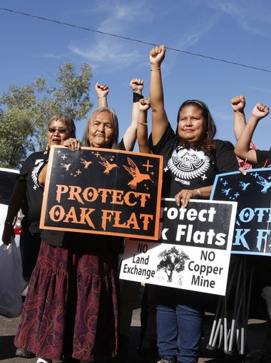 Women pose for a photo holding signs in solidarity with the San Carlos Apache tribe resistance to the development of a copper mine in Oak Flat. They attended the first celebration of the Indigenous Peoples Day in Phoenix on Oct. 10, 2016.