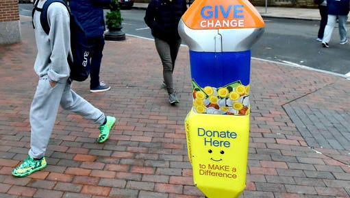 In this Monday, Dec. 12, 2106 photo, pedestrians pass one of four parking-style meters in New Haven, Conn., located in areas where panhandling has been prevalent. The city is among the latest to install meters to collect loose change from those who might otherwise give money to those begging on the street. There are plans to install six more to support local, nonprofit organizations that help the homeless. (Peter Hvizdak  /New Haven Register via AP)