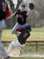 Penfield third baseman Gage Ziehl, top, reaches for