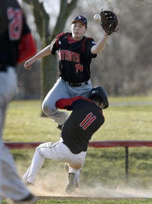 Penfield third baseman Gage Ziehl, top, reaches for the ball over Hilton base runner David Stirpe during a regular season game at Quest Elementary School on Monday, April 23, 2018. Penfield beat Hilton 6-5.