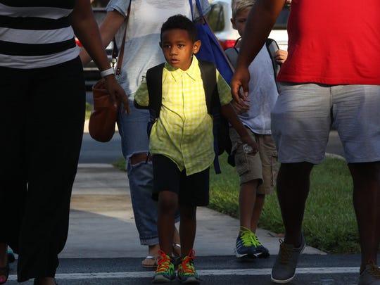 Landon Elder, 6, arrives at Pelican Marsh Elementary School for his first day of kindergarten Monday in Naples.