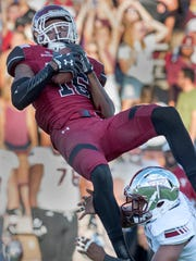 Aggies Jaleel Scott takes to the air to grab this pass over Troy's Kris Weatherspoon during the opening quarter of play Saturday night at Aggie Memorial Stadium. 9/16/17