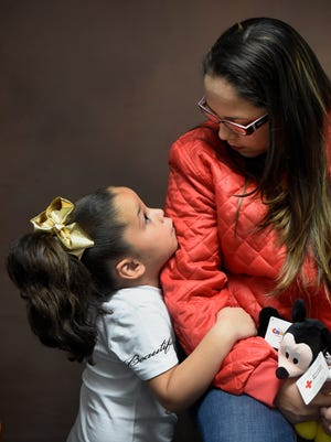 Marie Olivero comforts her daughter Nairielys Rodriguez, 5. Nairielys health was the impetus for leaving Puerto Rico.