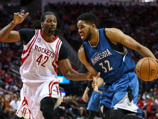 Minnesota Timberwolves center Karl-Anthony Towns (32) dribbles the ball as Houston Rockets center Nene Hilario (42) defends