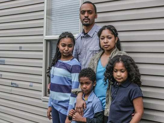 The Henry family stands in front of duct tape covering multiple bullet holes in the side of their Northwestside home.