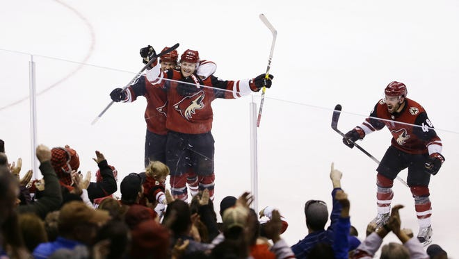 The Arizona Coyotes celebrate the winning goal by Nick Cousins against the New York Islanders in overtime on Jan. 22, 2018 at Gila River Arena in Glendale, Ariz.