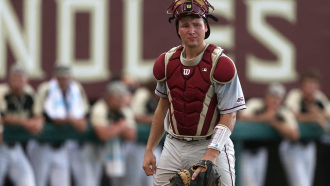 FSU's Cal Raleigh looks towards first base after throwing out a runner against UCF in the Seminoles 6-1 Regional Game win at Dick Howser Stadium on Saturday, June 3, 2017.