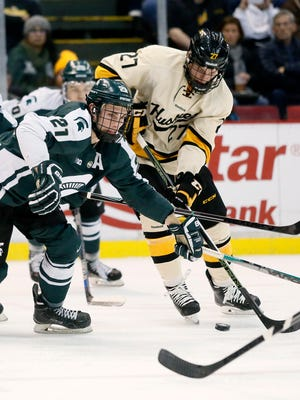 Michigan State's Joe Cox (21) battles for a puck against Michigan Tech's Tyler Heinonen (27) during the second period of the Great Lakes Invitational Tuesday at Joe Louis Arena.