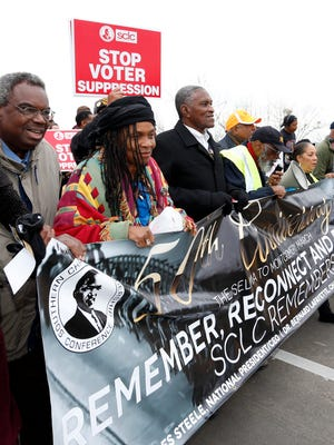 """Marchers hold a sign as they cross Edmund Pettus Bridge marching towards Montgomery Monday, March 9, 2015, in Selma, Ala. The weekend marked the 50th anniversary of """"Bloody Sunday,"""" a civil rights march in which protesters were beaten, trampled and tear-gassed by police at the Edmund Pettus Bridge in Selma, Ala."""