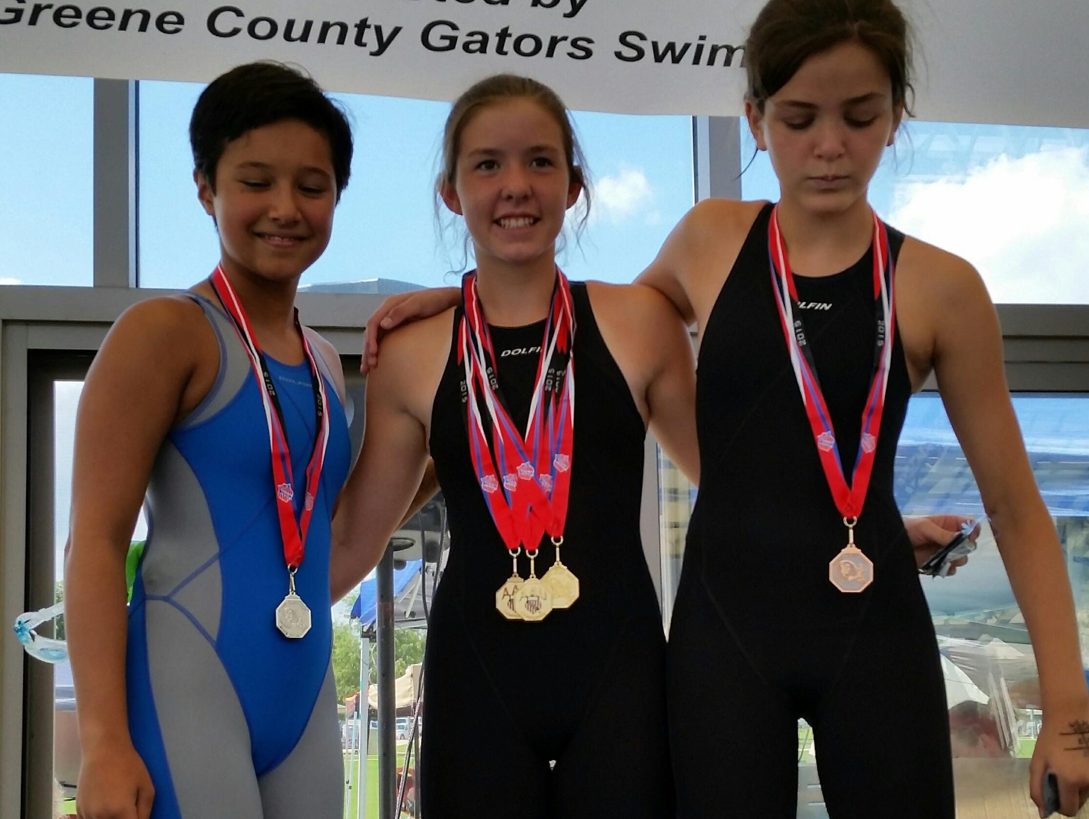 Mountain Home Hurricane swimmers Joia Traver (second), Mallory Brownrigg (first) and Madelyn Lynch (third) stand on the podium after their sweep in the 100-yard backstroke over the weekend at Paragould.