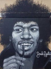 An inquisitive Jimi Hendrix with wandering eyes looking at you from a wall on what used to be the Sidebar Theatre.