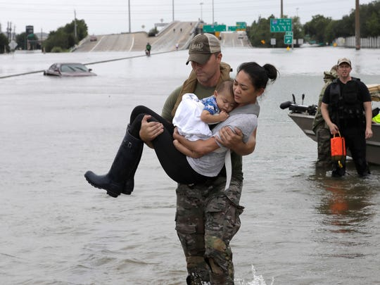 Houston Police SWAT officer Daryl Hudeck carries Connie Pham and her 13-month-old son Aiden after rescuing them from their home surrounded by floodwaters from Tropical Storm Harvey Sunday in Houston. The remnants of Hurricane Harvey sent devastating floods pouring into the city, sending thousands scrambling to rooftops or higher ground.