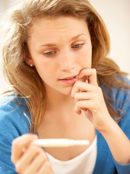 Teen girl looking at pregnancy test