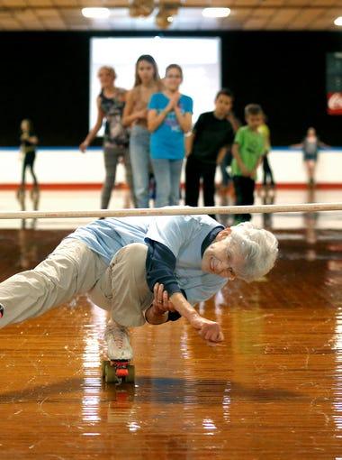 Eighty two-year-old Joanie Clark tries to avoid hitting a limbo bar at Skateland Sunday, Feb. 21, 2016.
