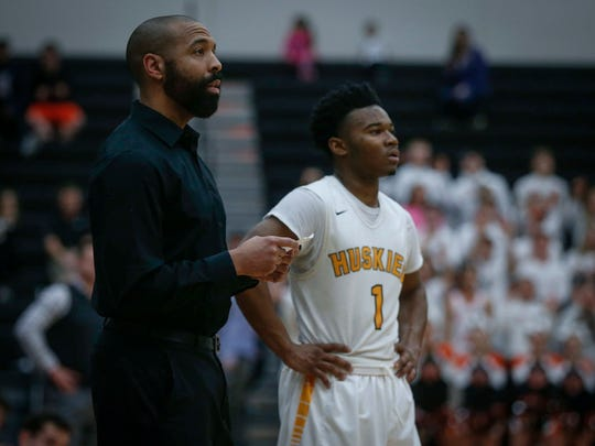 Hoover head boys basketball coach Courtney Henderson makes note of the floor before sending players in against Valley High as sophomore guard Kenny Quinn stands ready to play in the Class 4A substate 8 basketball game on Tuesday, Feb. 28, 2017, at Ankeny Centennial High School in Ankeny.