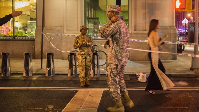 People try to access the area near the scene of an explosion on West 23rd Street and 6th Avenue as members of the military stand guard in Manhattan's Chelsea neighborhood, in New York, early Sunday, Sept. 18, 2016. An explosion rocked the block of West 23rd Street between Sixth and Seventh Avenues at 8:30 p.m. Saturday. Officials said more than two dozen people were injured. Most of the injuries were minor. (AP Photo/Andres Kudacki)