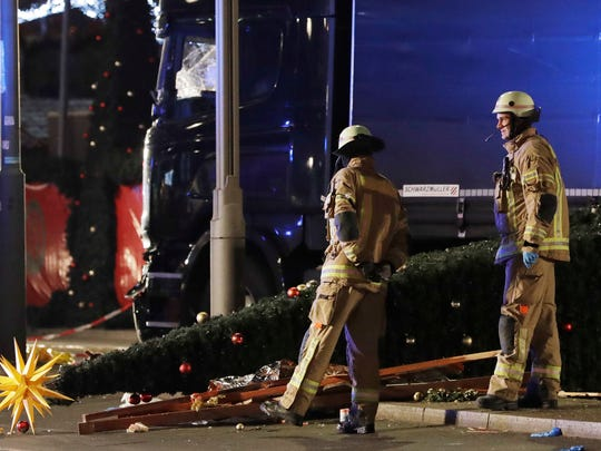 Firefighters look at a toppled Christmas tree after a truck ran into a crowded Christmas market and killed several people in Berlin, Germany, Monday, Dec. 19, 2016.