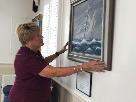 Barbara Dewhirst, staff at the House of Refuge Museum prepares Curt Whiticar's paintings for exhibit at the House of Refuge Museum.